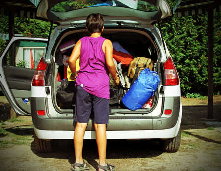 loads: boy loads his bags in the car after the holidays
