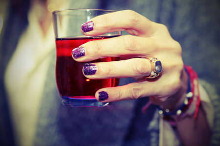 elegant womans hand that holds the glass