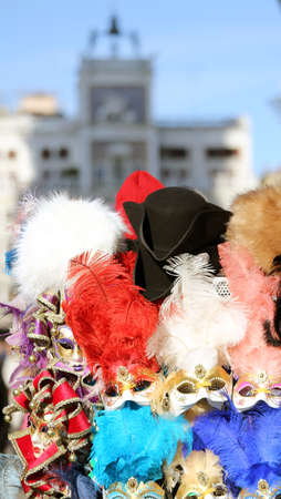 carnevale: masks for sale and the clocktower in saint mark square in Venice Italy