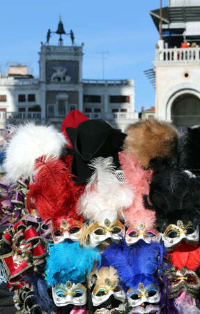 carnevale: masks and the clocktower in saint mark square in Venice Italy