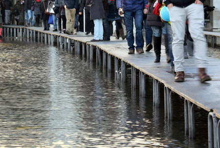 People walkingonthecatwalk in Venice Italy during at high tide photo