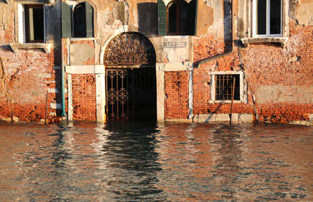 the flood tide: house on the Grand canal with the water in the door at high tide in Venice in italy