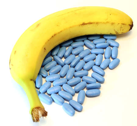 yellow banana with many blue pills for male problems Stock Photo