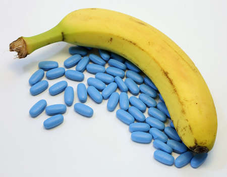 yellow banana with many blue pills for male problems Foto de archivo