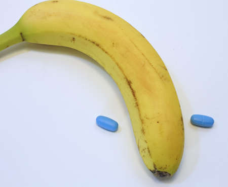 yellow banana with two blue pills for male problems Stock Photo
