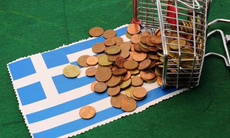 toppled: little shopping cart full of coins euro toppled over Flag of Greece Stock Photo