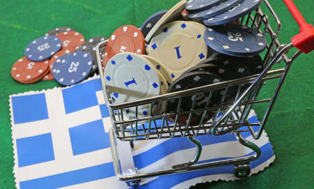 tokens: Shopping cart full of casino tokens over the flag of Greece to gamble Stock Photo