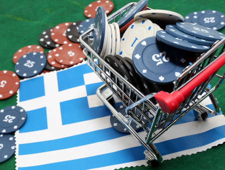 gamble: Shopping cart full of casino tokens over the flag of Greece to gamble Stock Photo