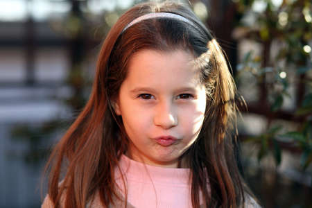 sulk: European sulky young girl outdoors in park Stock Photo