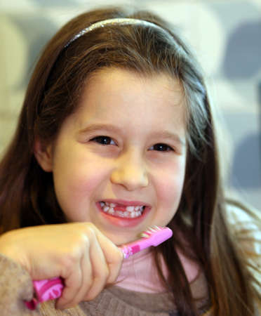 go inside: young girl without a tooth while brushing teeth in the bathroom