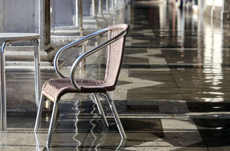the flood tide: single chair at high tide under the arcades during the flood in Venice  in italy
