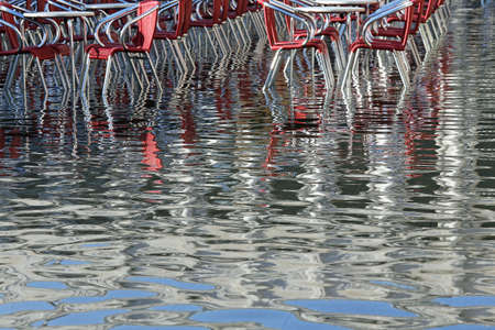 st  mark: Venice Italy, red chairs of a Restaurant in St Mark Square during high tide Stock Photo