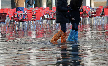 city people: people with plastic leggings and boots at high tide in Venice in Italy Stock Photo