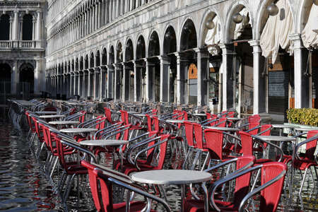 the flood tide: Venice, Historical Palace called Procuratie Vecchie in Saint Mark Square and the red chairs of the bar at high tide