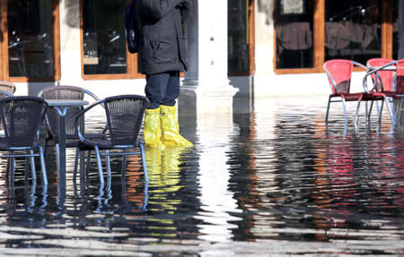 the flood tide: venice people with gaiters and boots at high tide in St. Marks square Stock Photo