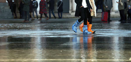 gaiters: venice people with plastic boots at high tide in St. Marks square Stock Photo