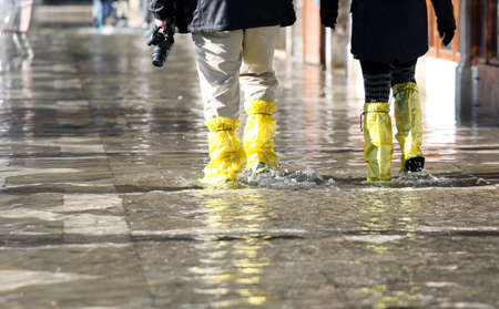 gaiters: venice photographer with yellowe gaiters at high tide in St. Marks square