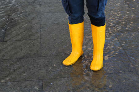 gaiters: venice woman with yellow boots at high tide in St. Marks square