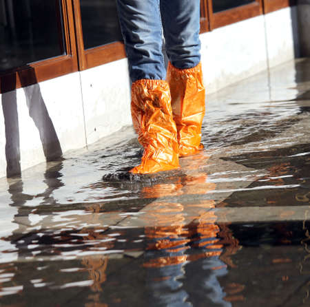 gaiters: venice woman with orange gaiters at high tide in St. Marks square