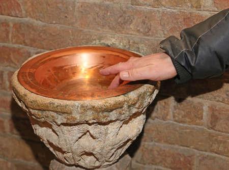 religion catolica: la mano del hombre y de una antigua fuente de agua bendita dentro de la Iglesia en un florero de cobre Foto de archivo
