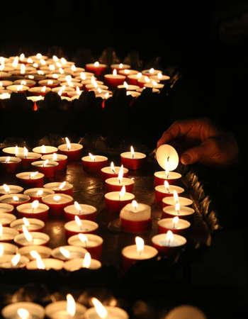 faithful: old faithful hand lights a candle in church
