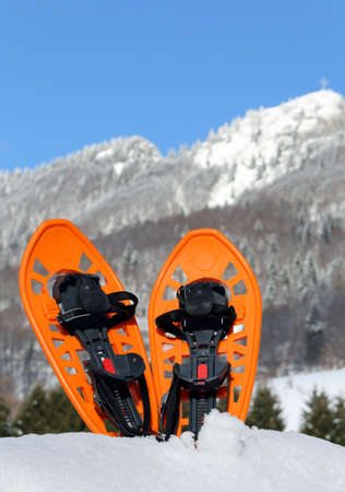 snowshoes: pari of orange modern snowshoes in the mountain Stock Photo