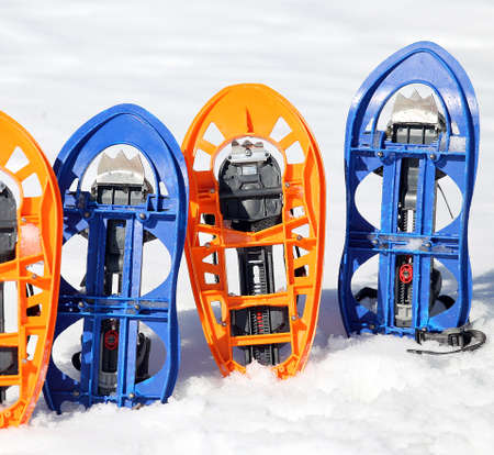snowshoes: two pari of orange modern snowshoes in the mountain