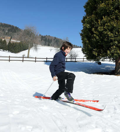 sportingly: child skiing falls with cross-country skis in mountains