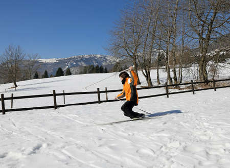 skiing accident: young boy for first time with cross-country skis on fresh snow falls in winter