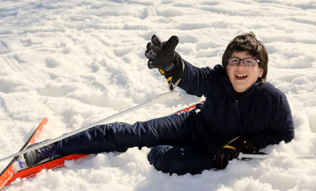 skiing accident: young boy asks for help after the fall on skis Stock Photo