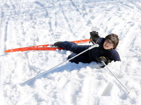 skiing accident: young boy asks for help after the fall on skis in winter