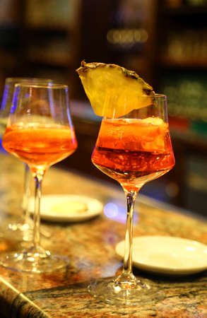bartenders: alcohol aperitif with a glass chalice at the bar and a slice of pineapple Stock Photo