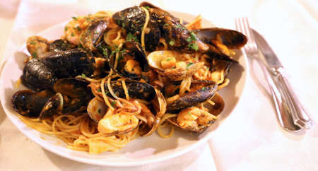 pastasciutta: huge plate of spaghetti with mussels and prawns in seafood restaurant