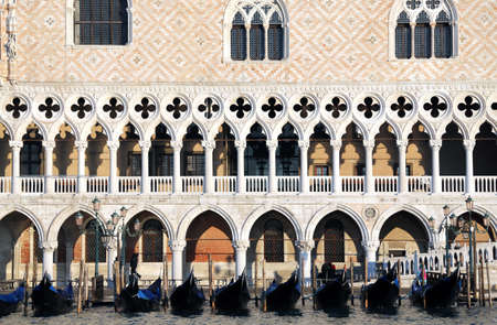 doges: Detail of Doges Palace in Venice with gondolas in Italy