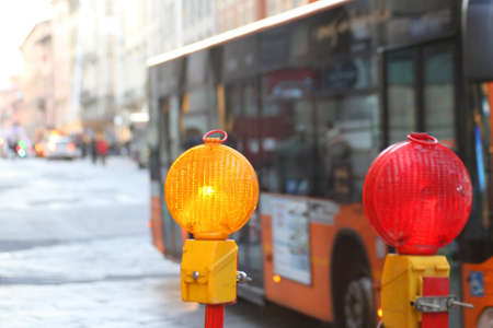 roadwork: yellow lamp and red lamp in roadworks in the city with a bus Stock Photo
