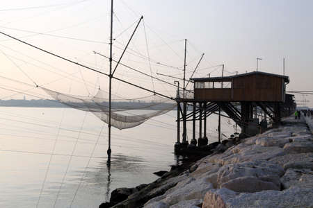lake dwelling: large Stilt House overlooking the sea and fishing nets of fishermen