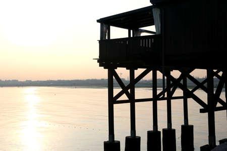 stilt house: large wooden stilt house on the seashore at sunset