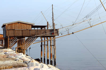 pile dwelling: large Stilt House ner the sea and fishing nets of fishermen Stock Photo