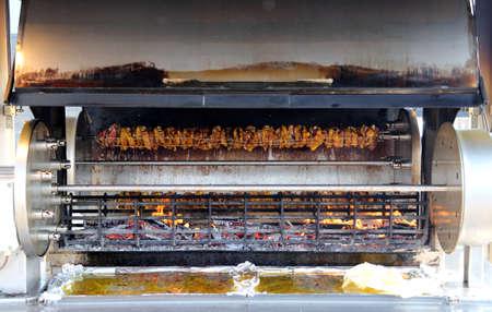 pollo rostizado: gran asador lleno de gallos y pollos asados