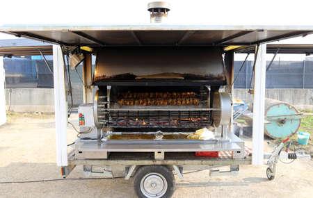 pollo rostizado: asador autom�tico con ruedas llenas de gallos y pollos asados