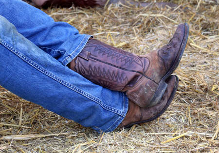 herder: Cowboy leather boots and a pair of jeans in the stable of the ranch