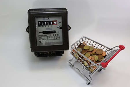 electricity meter: shopping cart full of European money and the old electricity meter Stock Photo