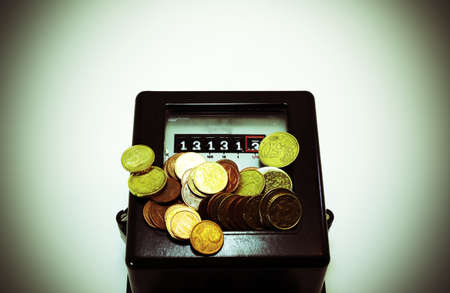 thirteen: obsolete counter of electrical energy consumption with the number thirteen in display and european coins Stock Photo