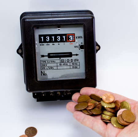electromechanical: meter and the hand full of European currencies