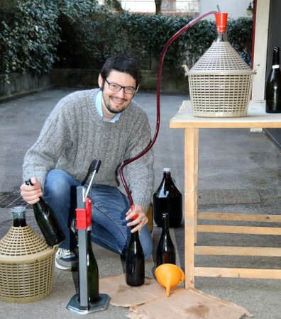 adult man pour red wine from the demijohn to glass bottles