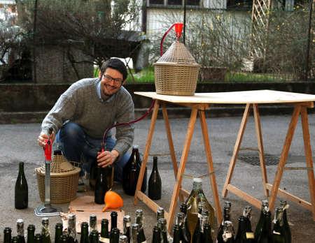 demijohn: smiling man pour red wine from the demijohn to glass bottles