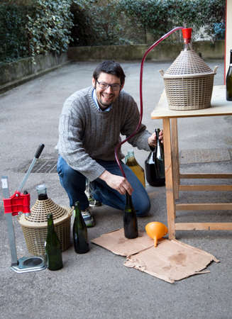 demijohn: Boy pour red wine from the demijohn to glass bottles Stock Photo