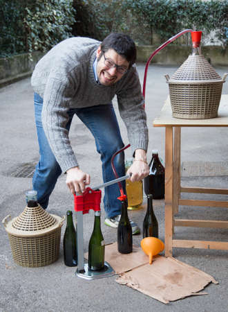 carboy: man white bottling red wine from the demijohn to glass bottles Stock Photo