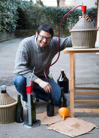 demijohn: man white bottling red wine from the demijohn to glass bottles Stock Photo