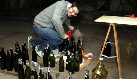 demijohn: man pour red wine from the demijohn to glass bottles
